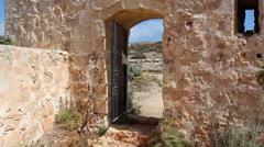 Gate In old wall with notices blowing in the wind from inside Stock Footage