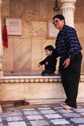 man with a small boy watching rats at karni mata temple, deshnok, india - stock photo