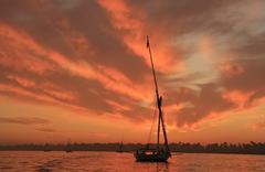 felucca boat sailing on the nile river at sunset, luxor - stock photo
