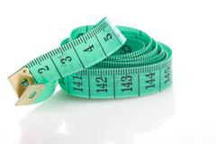 Green measuring tape, symbol of accuracy, on white Stock Photos