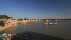 Panning- Gasisar Lake, Jaisalmer at sunset with colourful peddle/ row boats Stock Footage