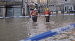 Emergency workers wading through flood water, Bradford on Avon, UK - stock footage