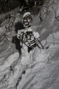 Skeleton corpse sitting in snow - stock photo