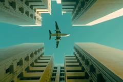 airplane flying over a building - stock photo