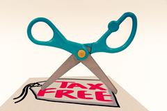 Blunt tipped scissor cutting through the word tax free Stock Photos