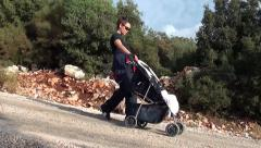 Mother with puchchair going down the hill 2 Stock Footage