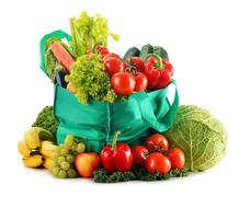 Green shopping bag with variety of fresh organic vegetables isolated on white Stock Photos