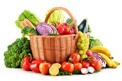Wicker basket with assorted organic vegetables and fruits  isolated on white Stock Photos