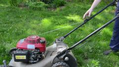 Gardener worker start grass lawn mower and cut grass Stock Footage