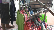 Stock Video Footage of A Market Trader Hangs Up Clothes