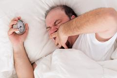 Man yawning as he tries to wake up Stock Photos
