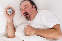 Lethargic man yawning as he struggles to wake up Stock Photos