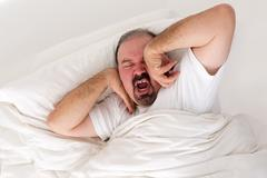 Tired man stretching in an effort to wake up Stock Photos