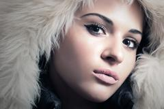 Fashion Portrait of Young Beautiful Woman in Fur Hood. Winter Style - stock photo