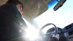 Low angle sun glaring on young driver driving a car Stock Footage