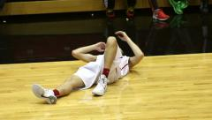 Basketball player laying down like he is hurting Stock Footage