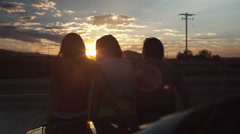 Three Teen Girls Leaning Against A Car, Watching The Sunset Stock Footage