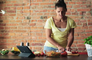 Stock Video Footage of Young woman preparing salad and checking recipe on tablet computer