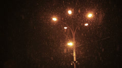Street lantern's yellow light in snowfall night Stock Footage