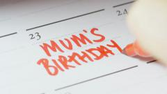 Writing Mum's birthday on calendar Stock Footage