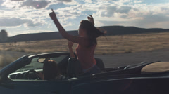 Teen Girl Standing In A Convertible Flaps Her Arms On A Road Trip Stock Footage