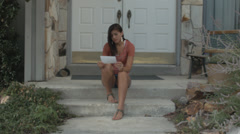 Beautiful Teen Girl Sits On Front Steps Reading Bad News Stock Footage