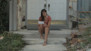 Stock Video Footage of Beautiful Teen Girl Sits On Front Steps Reading Bad News