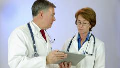 Consulting doctors review data using a tablet pc Stock Footage
