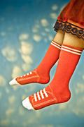 Stock Photo of close-up of legs of girl wearing red socks over clouds