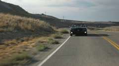 3 Girls Driving A Black Convertible In The Desert [Cyclist Passes In Opp. Lane] Stock Footage