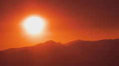 Large White Hot Sun In An Orange Glow Over Mountains Stock Footage