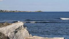Ocean and rock with Cape Neddick Nubble lighthouse Stock Footage