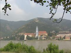 River Danube streaming + pan Durnstein village with baroque church and tower Stock Footage