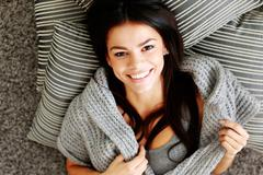 portrait of a young happy woman lying on the floor with pillows. view from ab - stock photo