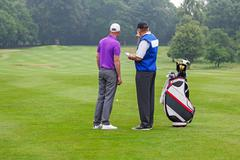 Caddy pointing out a hazard to golfer Stock Photos