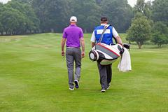 Golfer and caddy walking up a fairway Stock Photos