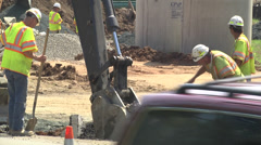 Backhoe and workmen Stock Footage