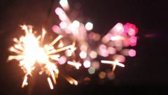 Sparkler with colorful fireworks in the back - stock footage