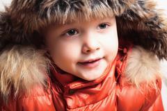 Child in fur hat and orange jacket. fashion kid.children.winter style Stock Photos