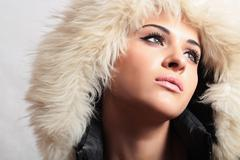 Stock Photo of Beautiful woman with fur. white fur hood. winter style. fashion beauty girl