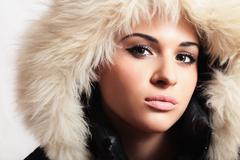 Stock Photo of Beautiful woman with fur. white fur hood. winter style