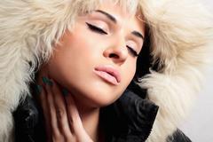 Beautiful fashion woman with fur. white fur hood. closed eyes Stock Photos