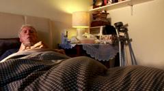 Post-op Elderly man eating in bed watching TV Stock Footage