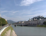 Stock Video Footage of Sacher Hotel + pan across river Salzach at skyline Salzburg Old Town