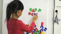 Little Asian Girl Spelling Happy New Year On Fridge Stock Footage