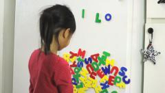 Little Asian Girl Spelling I Love Mom On Fridge Stock Footage
