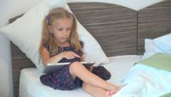 Child Playing a Game with Wireless Tablet, Ipad, Little Girl Learning ABC in Bed Stock Footage
