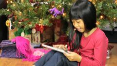 Little Asian Girl Using Tablet Beside Christmas Tree Stock Footage