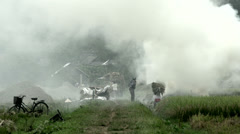 Smoke from burned hay and people working on farm land in Mai Châu Stock Footage