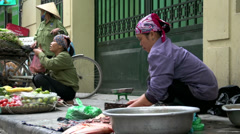 Woman cutting fish with on the background a woman selling vegetables Stock Footage
